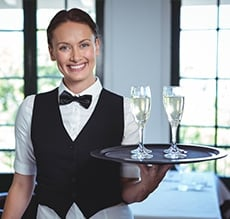 waitress serving two glasses of champagne